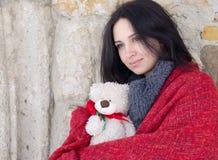 Retrato de una muchacha sonriente hermosa con el oso de peluche en invierno Foto de archivo libre de regalías