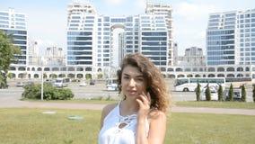Retrato de una muchacha sonriente hermosa con el pelo rizado contra la perspectiva de una ciudad moderna almacen de metraje de vídeo
