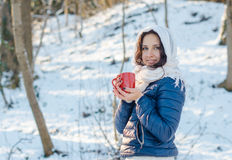 Retrato de una muchacha sonriente hermosa con la taza roja en bosque del invierno Fotos de archivo libres de regalías