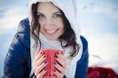 Retrato de una muchacha sonriente hermosa con la taza roja en bosque del invierno Imagenes de archivo