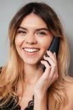 Retrato de una muchacha sonriente hermosa que habla en el teléfono móvil Foto de archivo