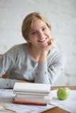 Retrato de una muchacha sonriente joven con los libros y la manzana Fotos de archivo