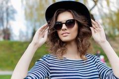 Retrato de una muchacha sonriente joven linda hermosa en un sombrero negro y gafas de sol en un estilo urbano Imagen de archivo