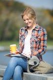 Retrato de una muchacha sonriente que se sienta en la lectura del puente Fotos de archivo libres de regalías