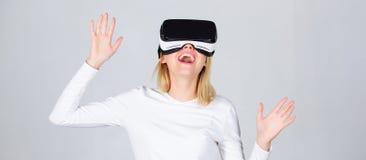 Retrato de una muchacha sorprendente que usa auriculares de la realidad virtual aisladas en fondo gris Exploración feliz de la mu fotografía de archivo libre de regalías