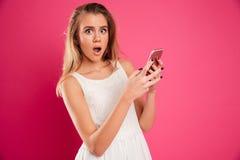 Retrato de una muchacha sorprendida en el vestido que sostiene el teléfono móvil Fotografía de archivo