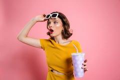 Retrato de una muchacha sorprendida en las gafas de sol que sostienen la taza foto de archivo