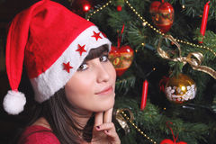 Retrato de una muchacha triguena atractiva con el sombrero de la Navidad Imágenes de archivo libres de regalías