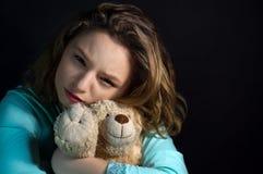 Retrato de una muchacha triste con el oso de peluche Imagen de archivo