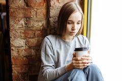 Retrato de una muchacha triste que se sienta en el travesaño de la ventana y el café de consumición Fotos de archivo