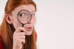 Retrato de una mujer adolescente del pelo rojo joven que mira la cámara a través de una lupa Foto de archivo