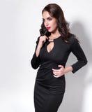 Retrato de una mujer adulta hermosa de la sensualidad en el vestido negro que presenta sobre el fondo blanco Vista en el lado Fotos de archivo libres de regalías