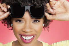 Retrato de una mujer afroamericana alegre que sostiene las gafas de sol sobre fondo coloreado foto de archivo libre de regalías
