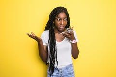 Retrato de una mujer afroamericana joven emocionada que habla en el teléfono móvil mientras que se coloca aislado sobre fondo ama imágenes de archivo libres de regalías