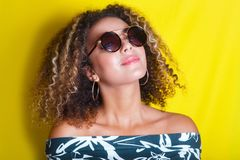 Retrato de una mujer afroamericana joven en gafas de sol Fondo amarillo lifestyle foto de archivo