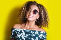 Retrato de una mujer afroamericana joven en gafas de sol Fondo amarillo lifestyle fotografía de archivo libre de regalías