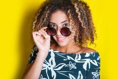 Retrato de una mujer afroamericana joven en gafas de sol Fondo amarillo lifestyle fotos de archivo libres de regalías