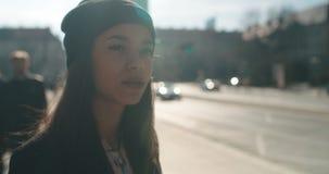 Retrato de una mujer afroamericana joven que espera un taxi o un autobús, al aire libre almacen de metraje de vídeo