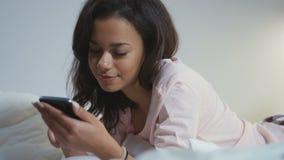 34040de915032 Retrato de una mujer afroamericana joven sonriente que miente en cama con  el teléfono móvil almacen