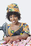 Retrato de una mujer afroamericana que usa la máquina de coser sobre fondo gris fotografía de archivo