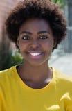 Retrato de una mujer afroamericana típica en una camisa amarilla Fotografía de archivo
