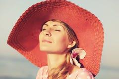 Retrato de una mujer agraciada hermosa en sombrero rosado elegante con un borde ancho Belleza, concepto de la manera Imagen de archivo