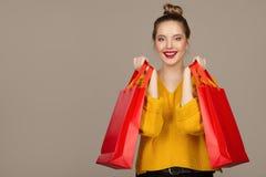 Retrato de una mujer alegre feliz que sostiene bolsos que hacen compras rojos fotos de archivo libres de regalías