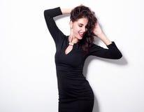 Retrato de una mujer alegre hermosa de la sensualidad en el vestido negro que presenta sobre el fondo blanco Fotografía de archivo libre de regalías