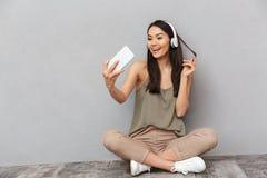 Retrato de una mujer asiática feliz que se sienta en un piso Imágenes de archivo libres de regalías
