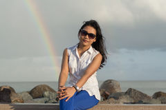 Retrato de una mujer asiática hermosa joven en las gafas de sol que se sientan con el arco iris en el fondo Fotos de archivo libres de regalías
