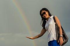 Retrato de una mujer asiática hermosa joven en las gafas de sol que sostienen el arco iris disponible Imágenes de archivo libres de regalías