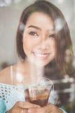 Retrato de una mujer asiática joven magnífica que se relaja con la taza de ho Imágenes de archivo libres de regalías