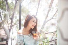 Retrato de una mujer asiática joven que bebe su té de la mañana sobre a Imagen de archivo