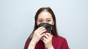 Retrato de una mujer asiática joven que lleva una máscara protectora negra almacen de video