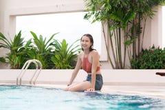 Retrato de una mujer asiática joven que se sienta por la piscina con los pies en wat Fotos de archivo libres de regalías