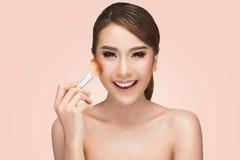 Retrato de una mujer asiática que aplica la fundación tonal cosmética seca en la cara usando cepillo del maquillaje Foto de archivo