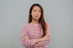 Retrato de una mujer asiática triste que se coloca con los brazos doblados Fotografía de archivo