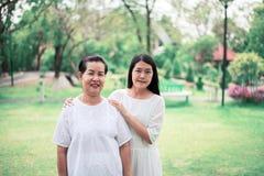 Retrato de una mujer asi?tica mayor con las mujeres jovenes que caminan en el parque junto, felices y la sonrisa foto de archivo