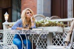 Retrato de una mujer asombrosa con mirada de moda que sueña sobre algo durante resto en cafetería al aire libre, Fotos de archivo libres de regalías