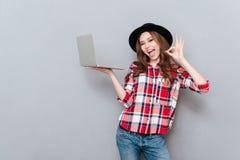 Retrato de una mujer atractiva en la camisa de tela escocesa que sostiene la PC Imagen de archivo libre de regalías