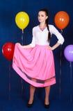 Retrato de una mujer atractiva joven cerca de muchos globos brillantes Foto de archivo libre de regalías