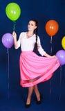 Retrato de una mujer atractiva joven cerca de muchos globos brillantes Foto de archivo