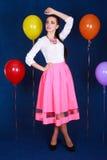 Retrato de una mujer atractiva joven cerca de muchos globos brillantes Fotografía de archivo