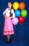 Retrato de una mujer atractiva joven cerca de muchos globos brillantes Fotos de archivo