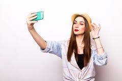 Retrato de una mujer atractiva joven con el sombrero que hace la foto del selfie en smartphone Imagen de archivo