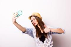 Retrato de una mujer atractiva joven con el sombrero que hace la foto del selfie en smartphone Fotos de archivo