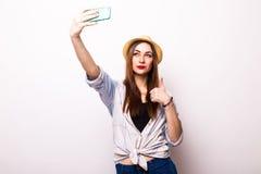 Retrato de una mujer atractiva joven con el sombrero que hace la foto del selfie en smartphone Imagenes de archivo