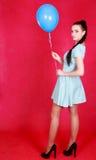 Retrato de una mujer atractiva joven que sostiene el globo azul Imagen de archivo