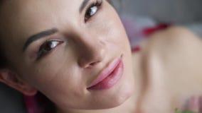 Retrato de una mujer atractiva que miente en el cuarto de baño con espuma y que sostiene una rosa rosada metrajes