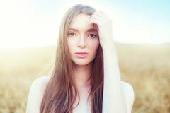 Retrato de una mujer atractiva sobre campo de trigo de oro en día de verano Imagen de archivo libre de regalías